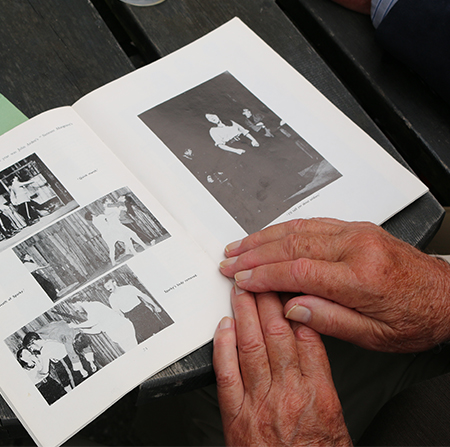 Hands placed on an old alumni magazine