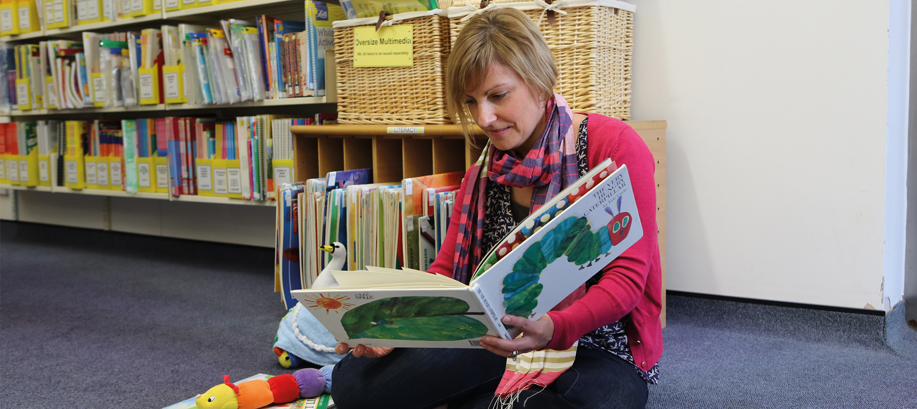 Student sat in school resources section of library reading a children's book