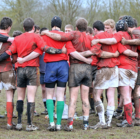 Rugby team stood in a huddle