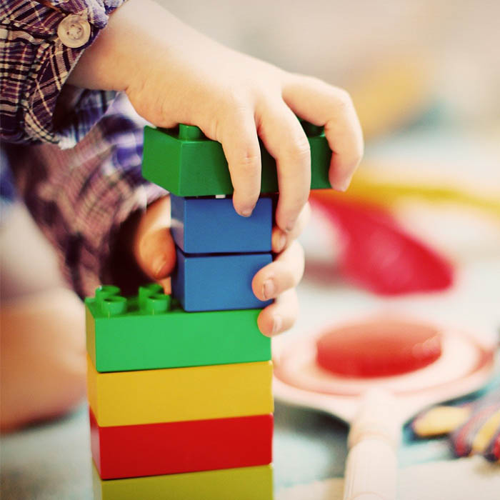 Child's hands playing with brightly coloured lego bricks