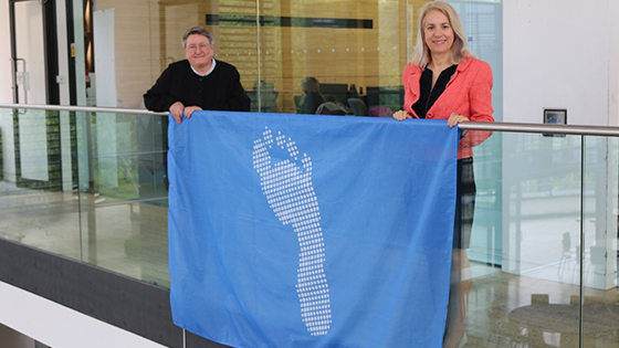 Joy Carter and Liz Stuart holding the blue footprint flag