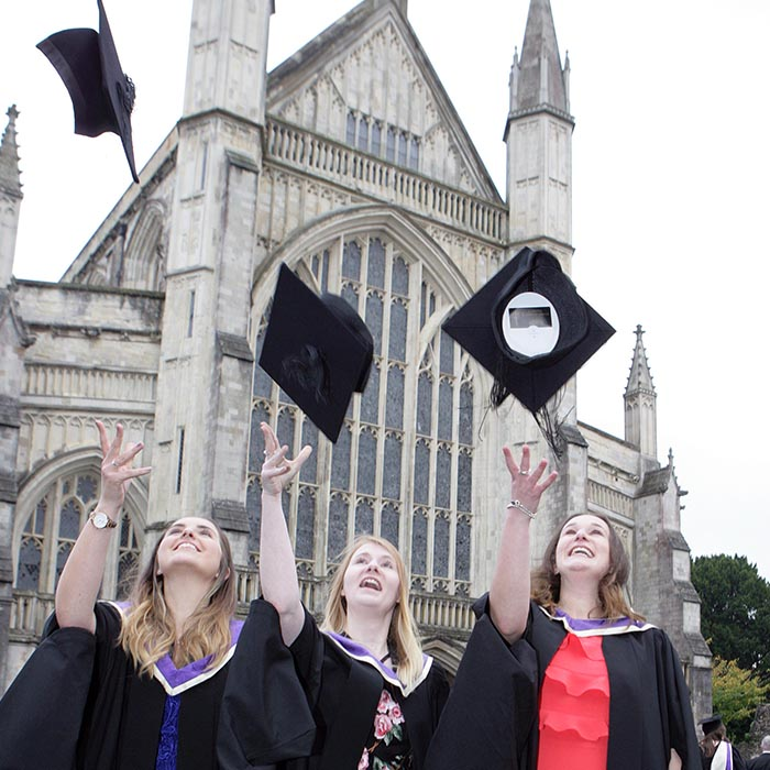 Three students throwing mortar boards in front of Winchester Cathedral