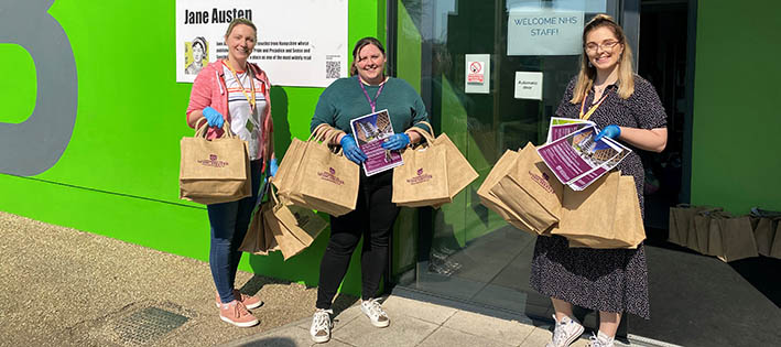 Three female staff with welcome bags standing outside halls of residence
