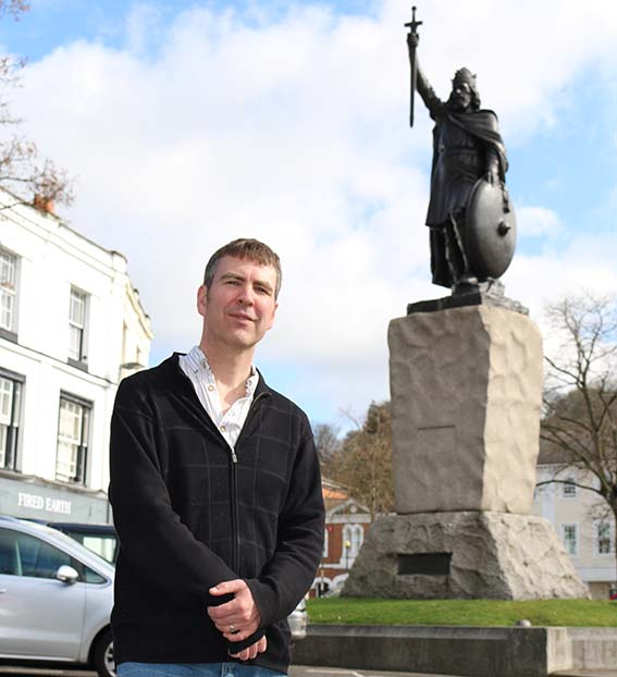 Man standing in front of King Alfred's statue in Winchester