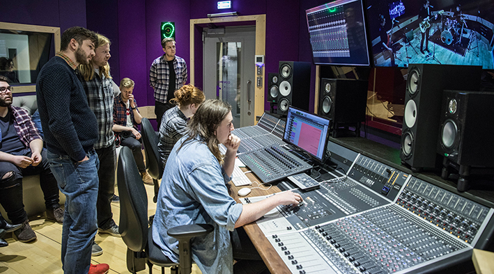 Man at the mixing desk in the recording studio watched by members of Alt-J