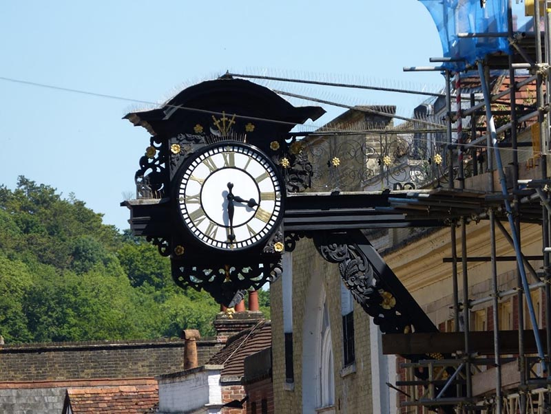 Ornate black clock on building in high street