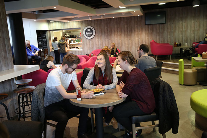 Students sat around a table eating chips in The Lounge at University of Winchester