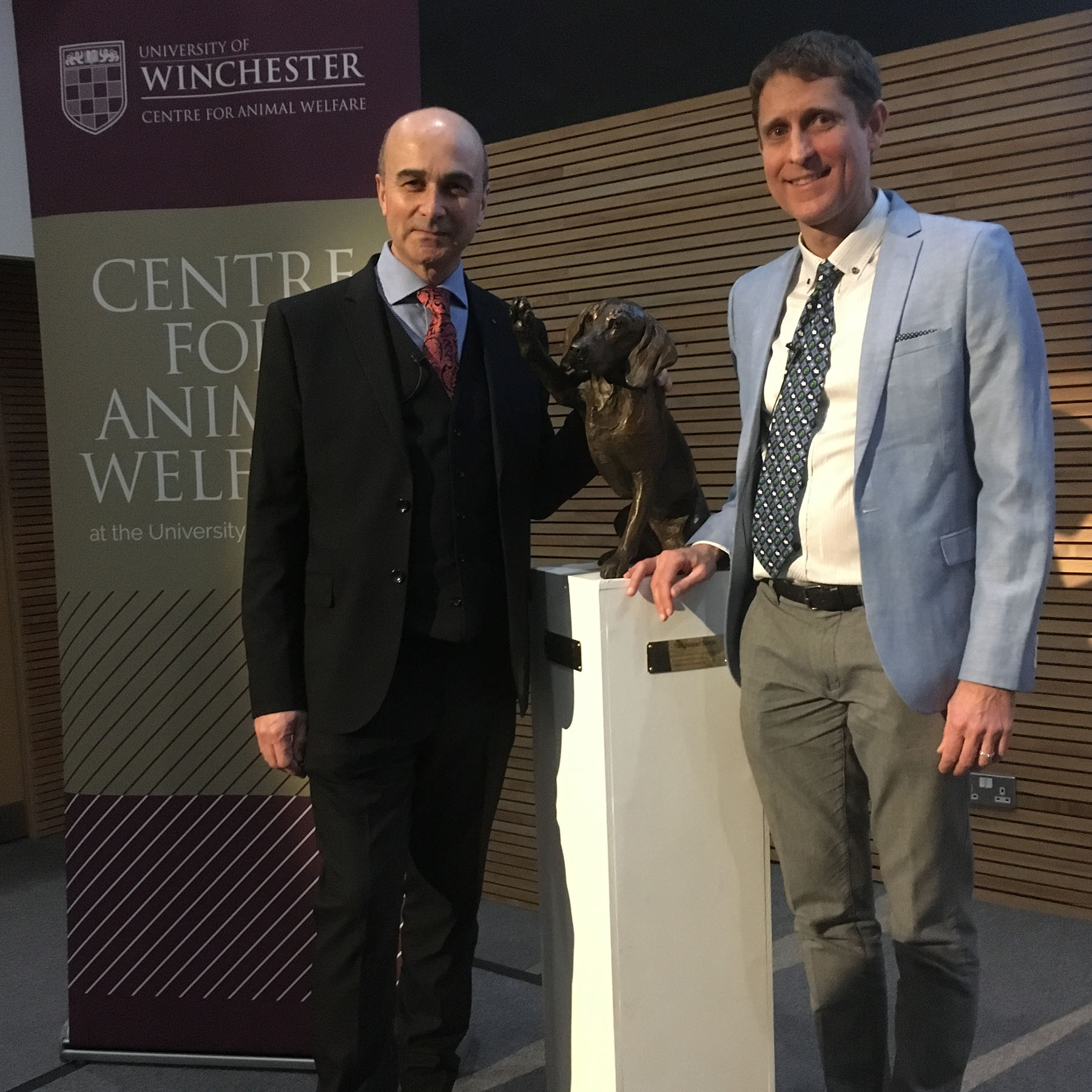 Animal qwelfare at Winchester: Compassion in World Farming CEO Phil Lymbery and Centre for Animal Welfare Director Andrew Knight by the CAW mascotte, a bronze dog with raised paw.