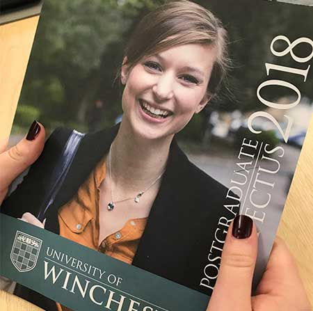 A student holding the 2018 postgraduate prospectus