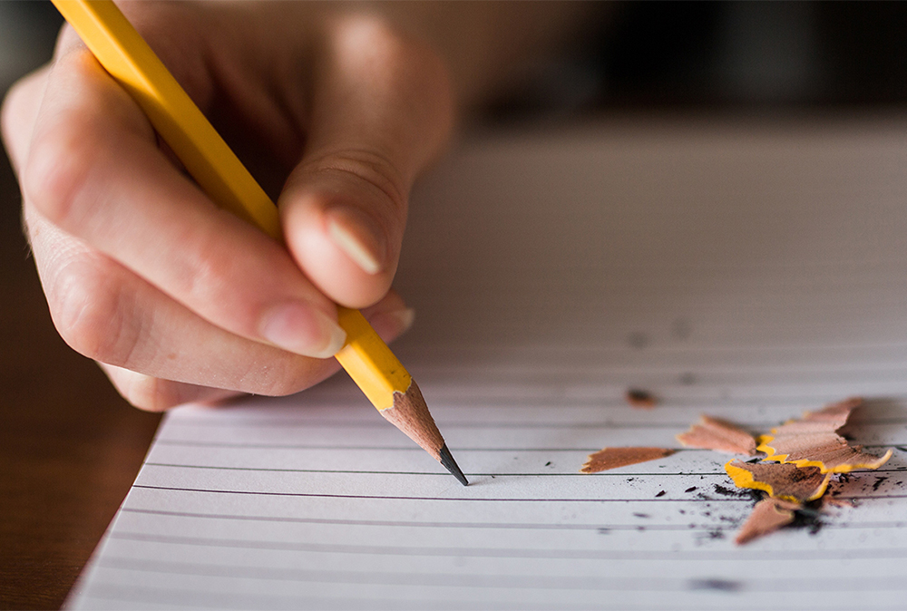 Person writing with a pencil in a notepad