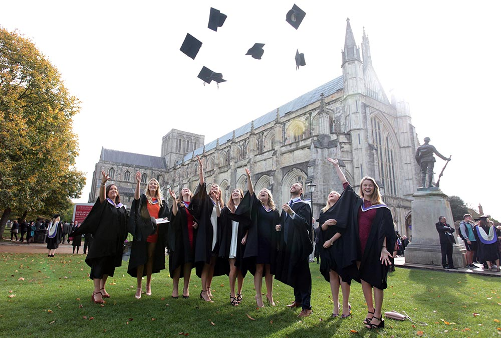 Group of students throwing their caps at the cathedral