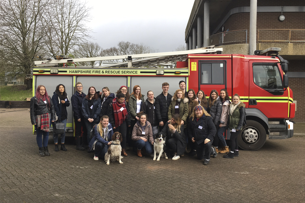 Group of students stood in front of a fire engine