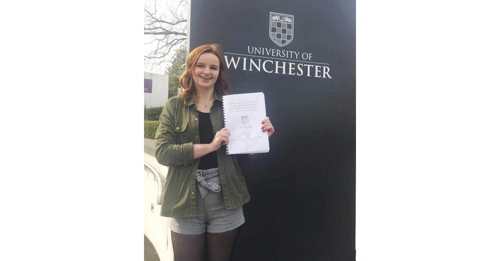 Third year female student holding her dissertation proudly